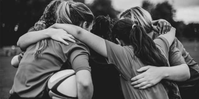 A black and white photo of teen rugby players huddled together, facing inwards in a cirlce and arms around each others' shoulders
