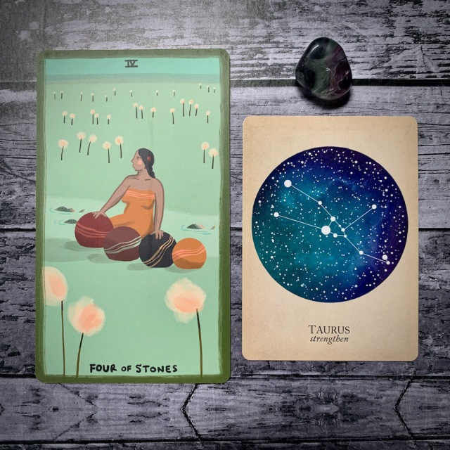 A photo of the tarot card for Four of Stones and the astrological card representing Taurus, along with a small crystal