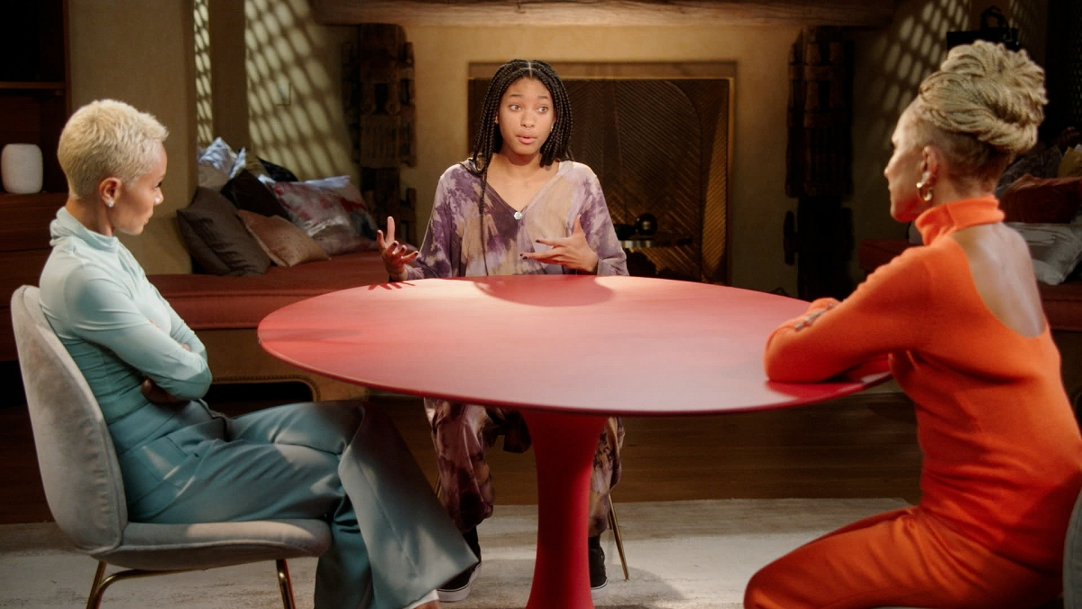Image shows 3 Black people (Gammy, Jada Pinkett Smith and Willow Smith) sitting around the infamous Red circle table in what looks to be a living room.