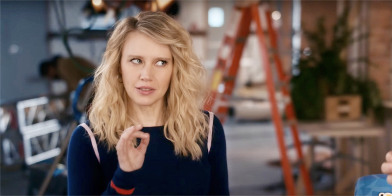 Kate McKinnon porte un sweat-shirt bleu marine avec les cheveux baissés, elle fait le symbole OK avec sa main droite et regarde sur le côté pour faire valoir son point.