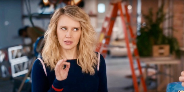 Kate McKinnon is in a navy blue sweatshirt with her hair down, she's making the OK symbol with her right hand and stares off to the side to make her point.