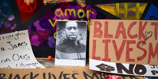 """A protest sign featuring the face of George Floyd with the inscription """"See You in Heaven"""" is laid on the ground next to a cardboard sign that reads """"Black Lives Matter"""" in red sharpie"""