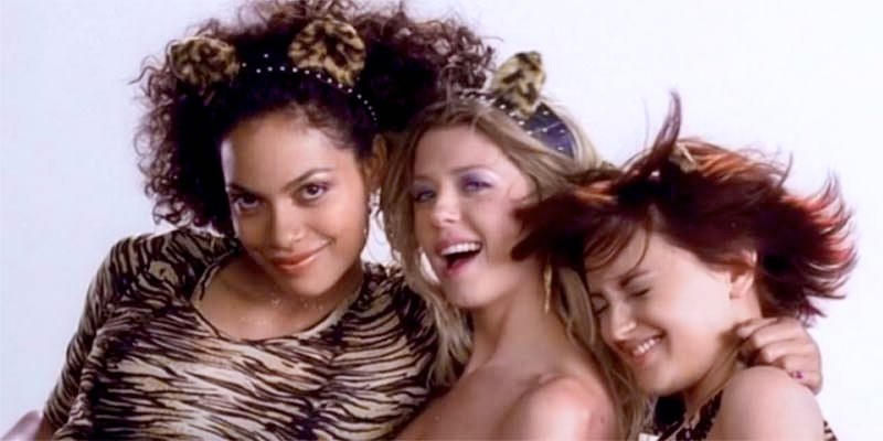 A press still from the movie Josie and the Pussycats in which all three girls, and their famed cat ear headbands, lean on each other while laughing and looking into the camera against a white background.