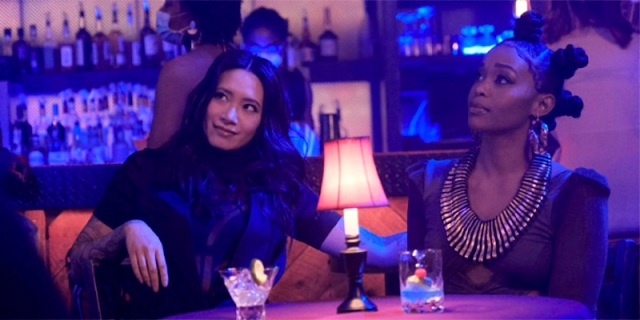 Grace and Anissa sit together at a table in sexy blue lighting.