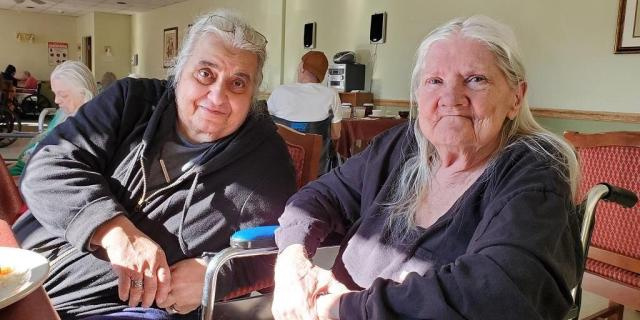 Two older women, Marie Giardino and Michaeljon Blue, sit next to each other at the Hornell Gardens nursing home. Blue is in a wheelchair.