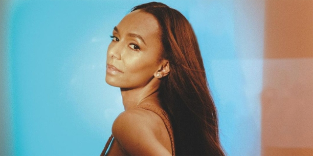 Janet Mock is against a blue background, lit in warm red tones