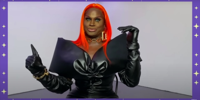 Drag Race 1325 Recap: LaLa Ri is wearing a leather dress with big shoulders, she has a bright orange wig