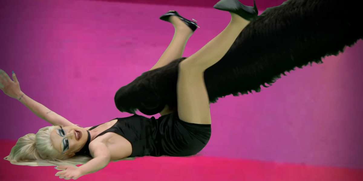Rupaul's drag race recap: Gottmik is in a little black dress lies on her back as a giant cat paw attacks her between her legs