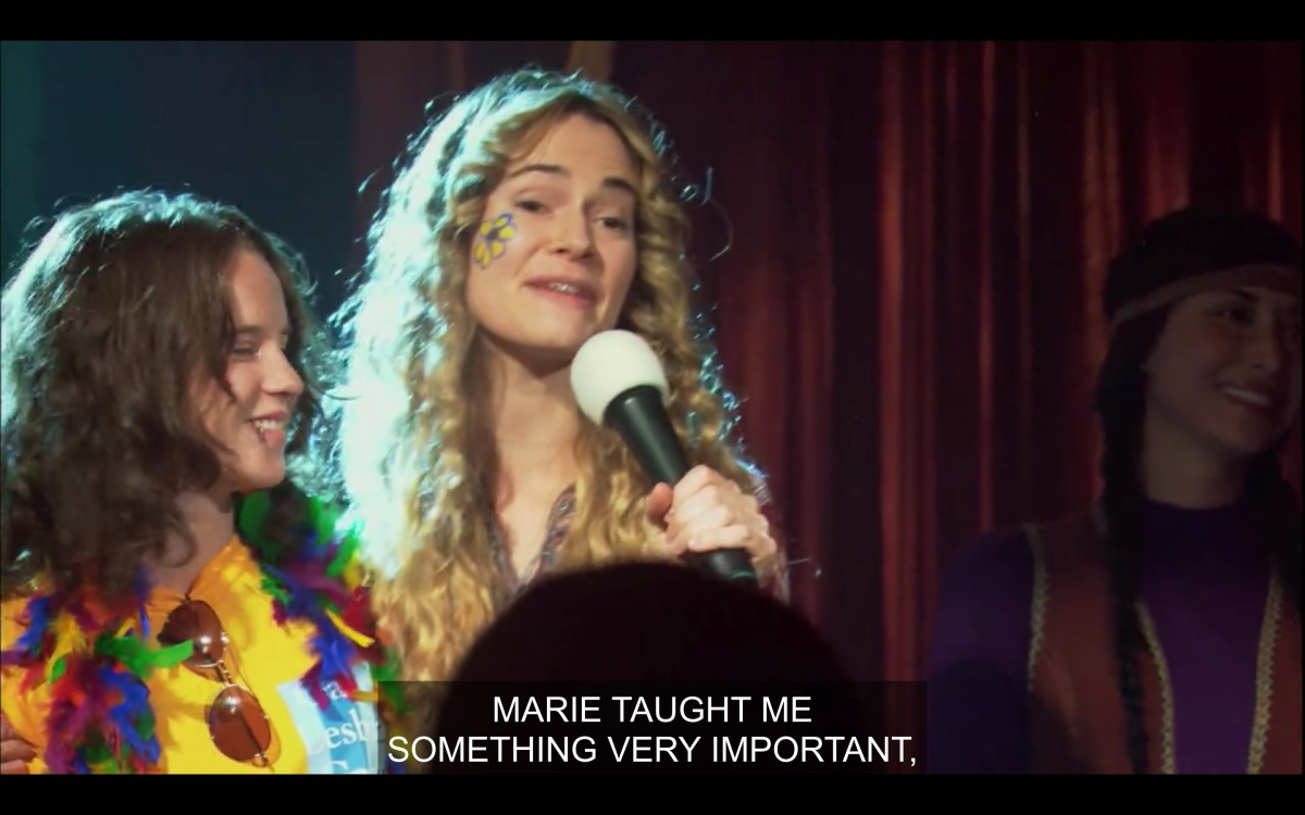 Alice on stage at the benefit with Marie saying Marie taught her something very important