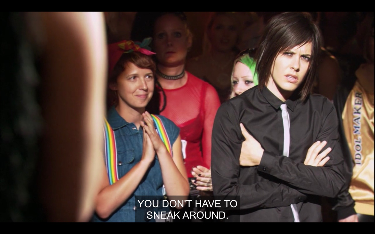 """Shane looking confused in the crowd with her arms crossed as Jenny, offsrcreen, says """"you don't have to sneak around anymore"""""""