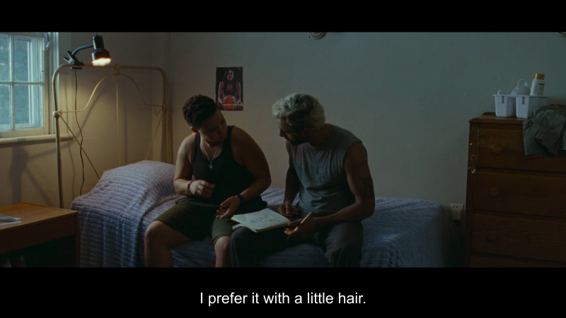Chelsea Lee and Riz Ahmed in Sound of Metal. They're sitting on a bad discussing a tattoo Ahmed's character drew. Subtitle: I prefer it with a little hair.