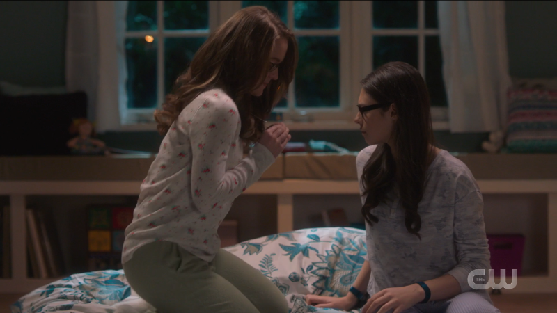 Kara shows Nia her necklace. They're both in PJs! It's very cute.