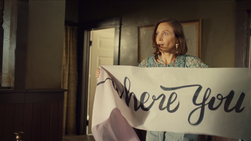 Waverly holds up a banner that almost definitely does not say WHORE but could if you look fast enough because cursive.