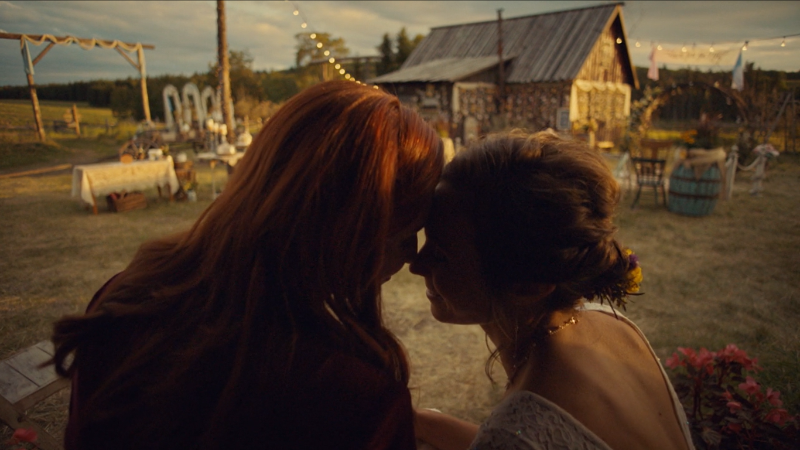 Waverly and Nicole press their foreheads together on the front porch of their forever home.