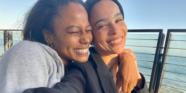 Zoe Kravitz and Taylour Paige are smiling together in the sunset against blue water and equally blue skies. Taylour's hands are draped over Zoe's shoulders.
