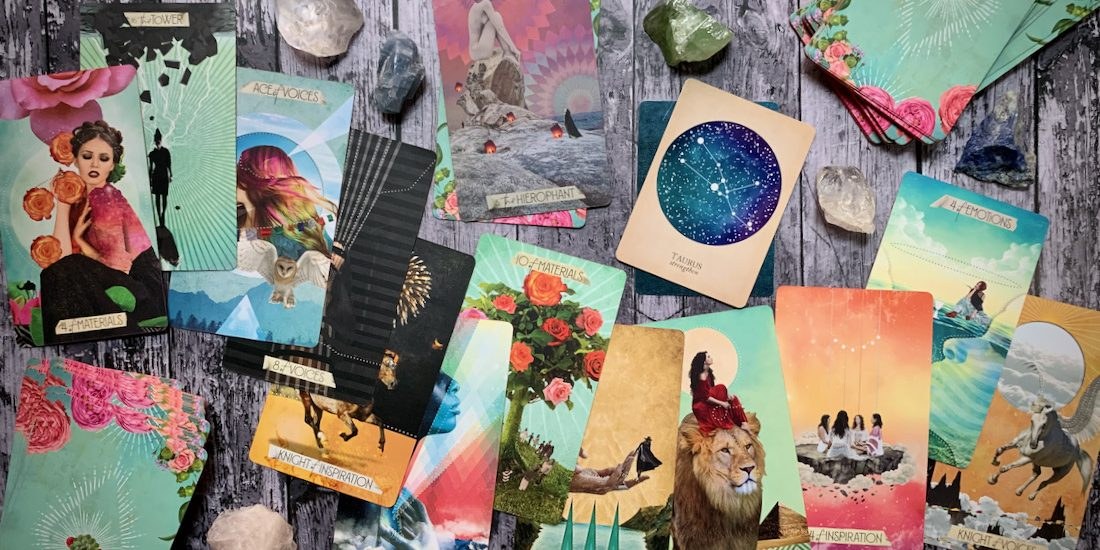 Dozens of colorful tarot cards scattered all over a wooden surface