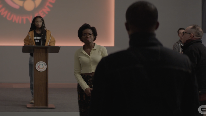 jordan and imani standing at the front of the room talking to a man whose back is to the camera