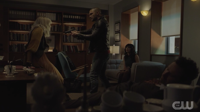 ocean points a gun at alice while enigma sits on the couch and jackson is still dead in his seat