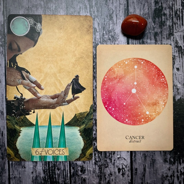 A tarot card for the 6 of voices, with a woman bowed over a body of water holding a small figure in her hand, a constellation card for Cancer: Distract; and a red crystal