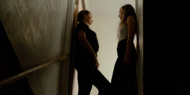Two women standing inside a doorframe in a dark space, turning to look at each other
