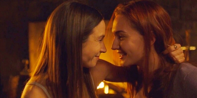 Waverly and Nicole smooch in front of a fireplace.