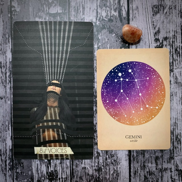 A tarot card for the 8 of Voices, which features a woman in harsh shadow, a constellation card that reads Gemini: Unite; and a variegated pink crystal