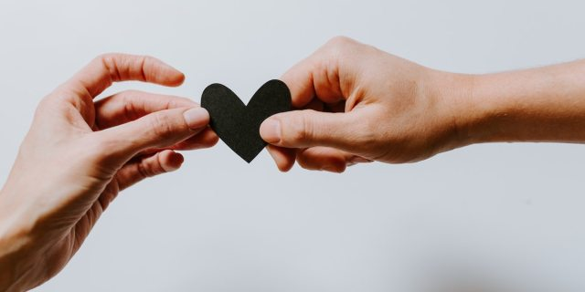 A stylized photo of two hands holding between them a black paper heart.