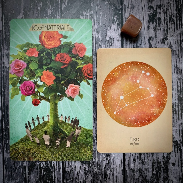 A tarot card for 10 of Materials featuring a group of people circled around a blooming tree; a constellation card reading Leo: Defeat, and a brown crystal