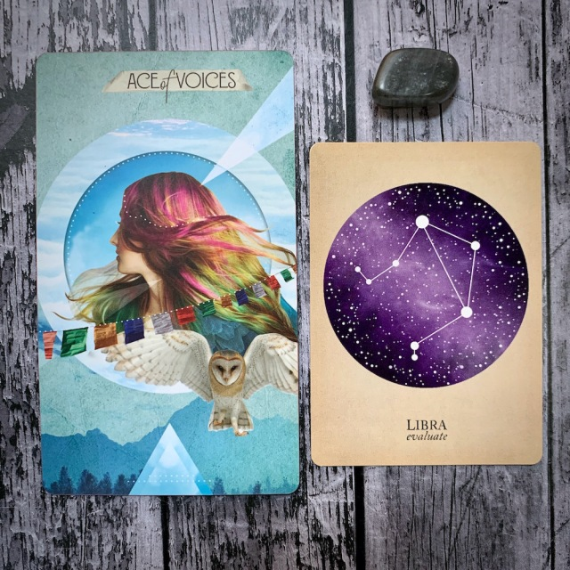 A tarot card for the Ace of Voices, featuring a woman with multicolored hair and a flying snowy owl; a constellation card reading Libra: Evaluate, and a gray crystal