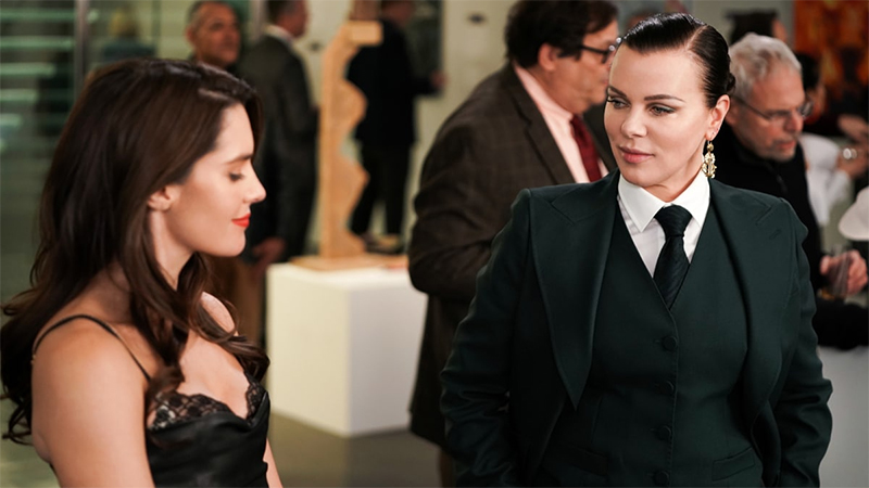 Debi Mazar as Maggie on Younger in a three-piece black suit talking to a woman in a cocktail dress at a party.