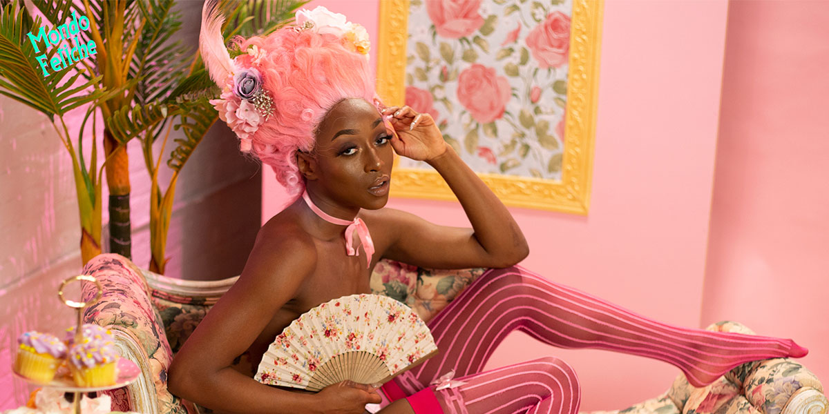 A Black femme with a pink Versailles wig and hot pink thigh high stockings posing on a flowered chaise.