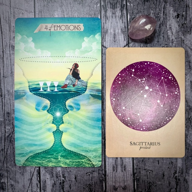 A tarot card for the 4 of Emotions, featuring a figure inside a giant goblet seemingly cast of water as they consider three other, smaller goblets, and two faces in profile seem about to kiss in the background. A constellation card reads Sagittarius: Protect, with a translucent lavender crystal.