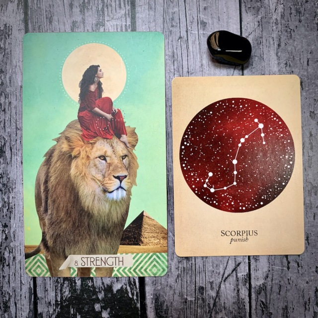 A tarot card for Strength, featuring a white woman in a red dress seated calmly astride a lion; a constellation card reading Scorpius: Punish, and a black crystal