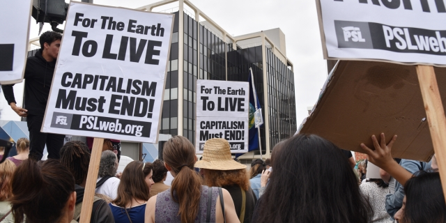A photo taken from the back of a crowd at a protest, featuring people holding signs that read FOR THE EARTH TO LIVE, CAPITALISM MUST END