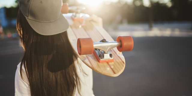 A photo from behind of a young woman with long straight hair wearing a snapback and hoisting a skateboard over her shoulder.
