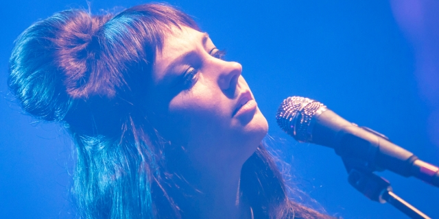 Angel Olsen, who came out as gay today, with long brunette hair and bangs, is photographed on stage, surrounded by blue lighting. There's a microphone in front of her.