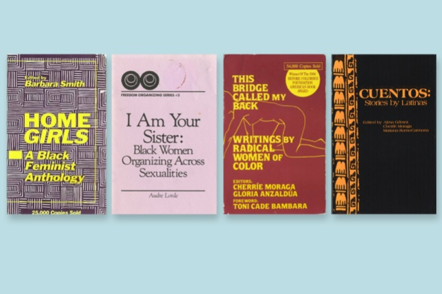 A collection of books, laid against a turquoise blue background.