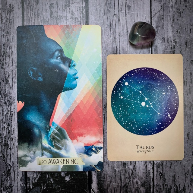 A photo of the tarot card Awakening, which features a Black woman's face in profile, the constellation card that read Taurus: Strengthen, and a grey crystal