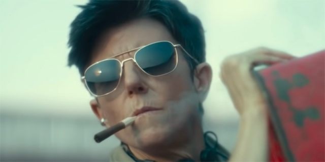 Tig Notaro in aviator sunglasses and a cigar, looking like a stone cold hottie.