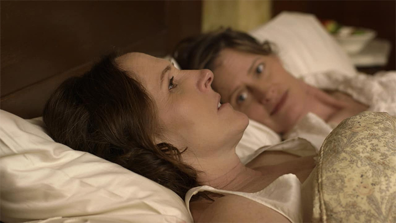 Emily and Sue lie in bed together