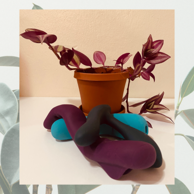Image shows 3 vibrators nestled together with a small plant behind it in the frame.