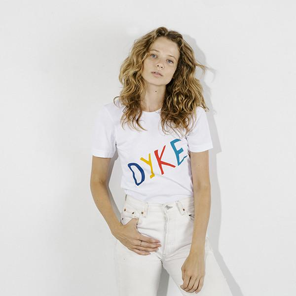 """Model in white t-shirt that says DYKE across it in large letters. The """"D"""" is royal blue, the """"Y"""" is yellow, the """"K"""" is read and the """"E"""" is teal."""