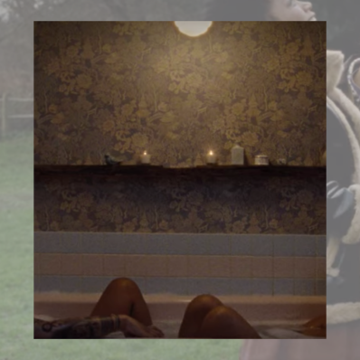 Image shows a photo of two people in a bathtub. You can only see their knees and wallpaper with candles lining the bath.
