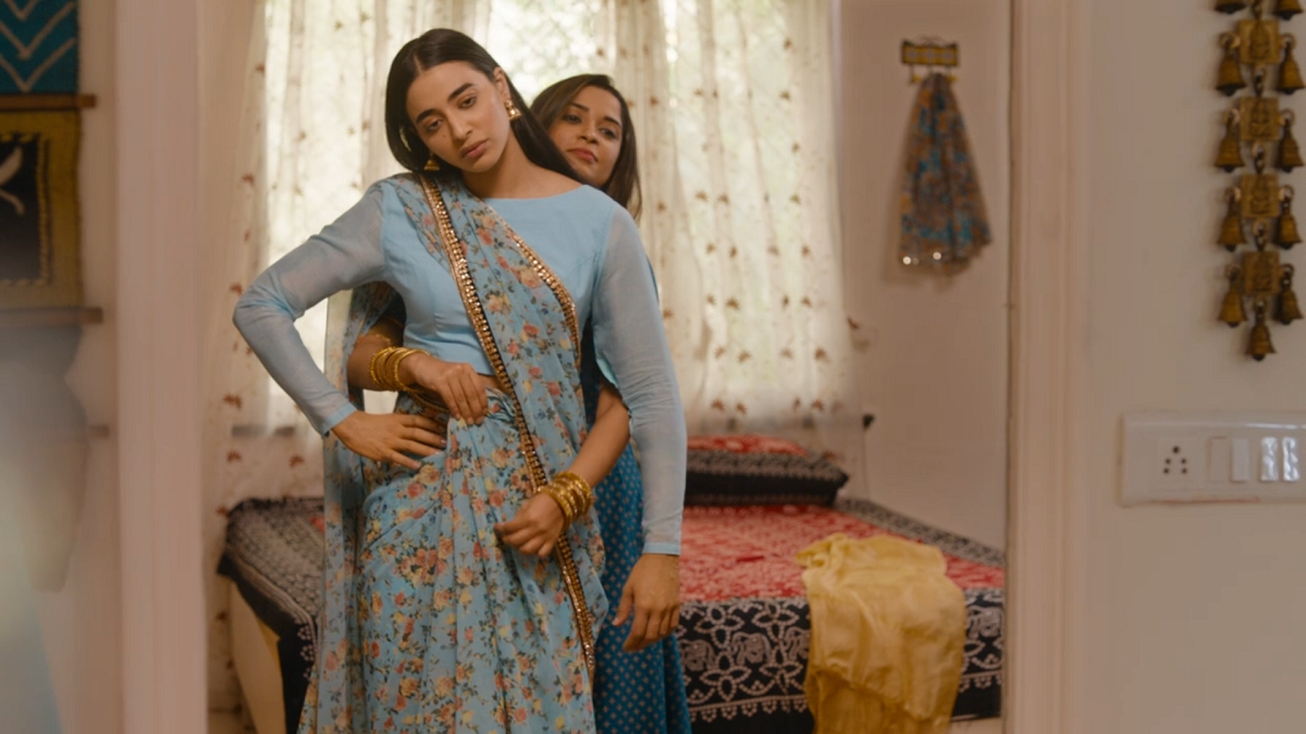 Umang's sister-in-law and ex, Pinky helps Umang get dressed in a pale blue sari. Pinky stands behind Umang setting the pleats in place, while Umang looks dejected.