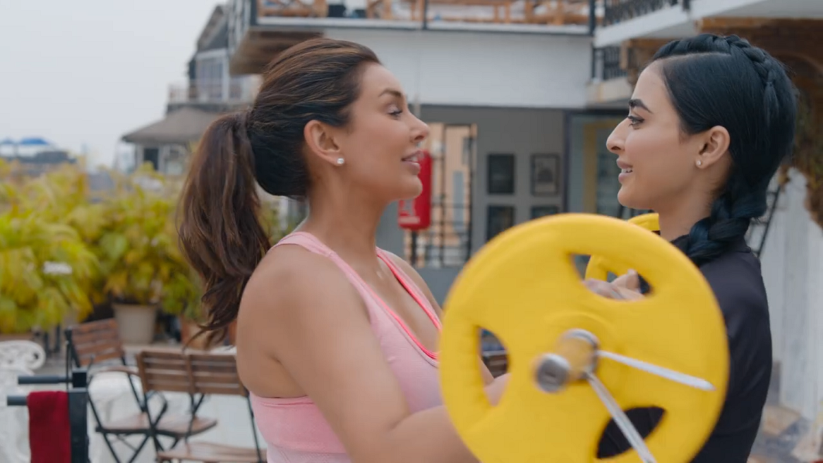 Standing on a rooftop in a peach-colored workout top, Lisa Ray, playing the character of Samara Kapoor hands a barbell to Umang, played by actress Bani J.