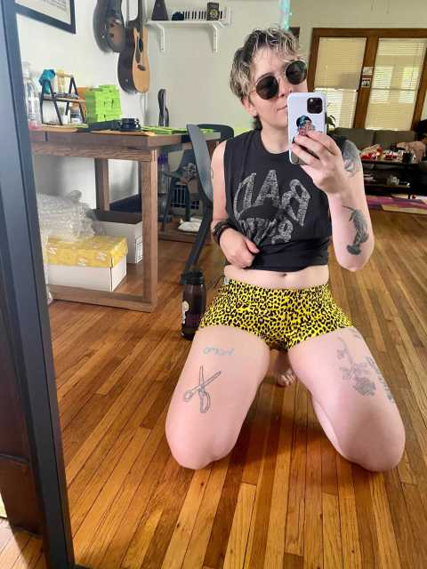 """Archie wears a black cutoff shirt that reads, """"BAD,"""" and leopard print swim shorts."""