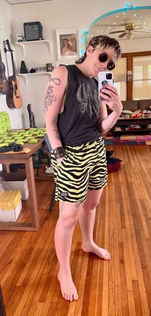 "Archie wears a black cutoff shirt that reads, ""BAD"" and zebra-print swim trunks"