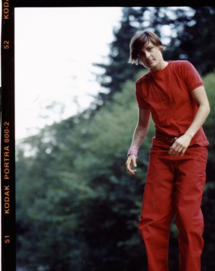 Daniela is wearing a matching red shirt and red pants. It looks like they're jumping.