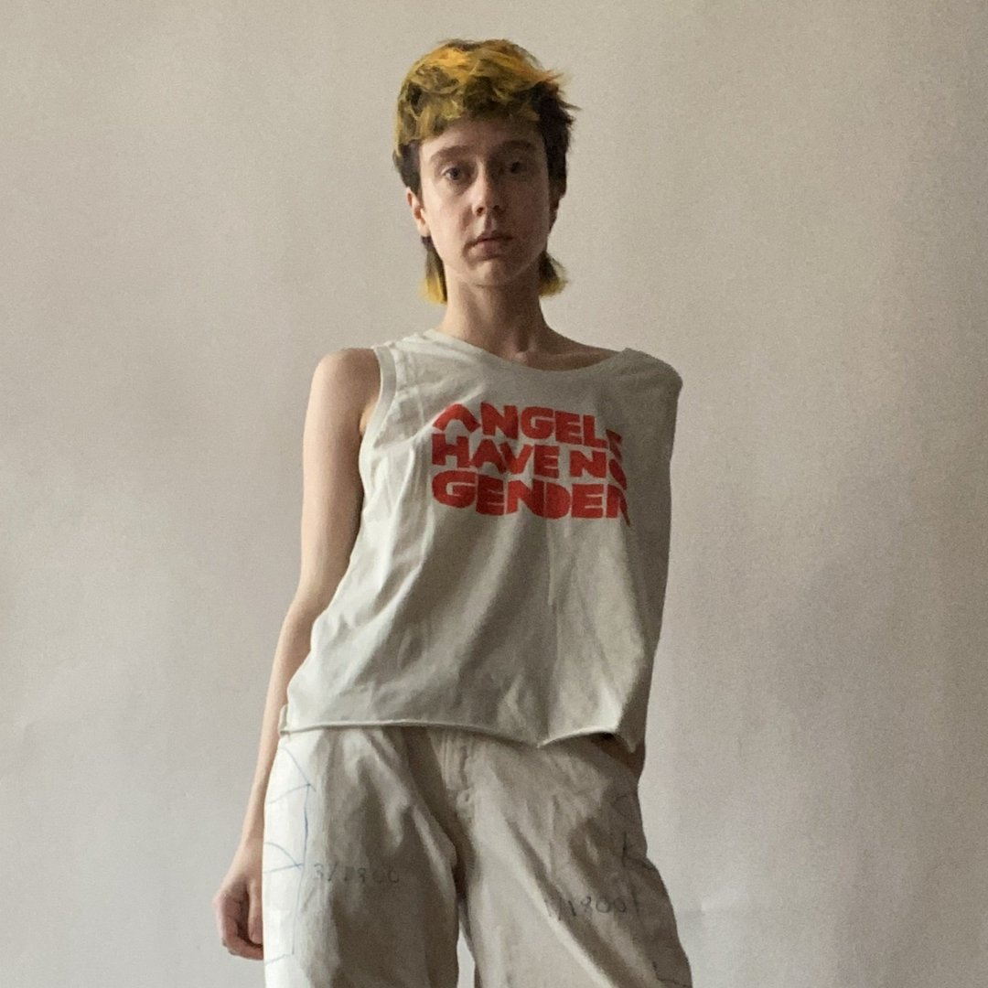 Model in beige pants and a sleeveless beige tee that reads ANGELS HAVE NO GENDER in red