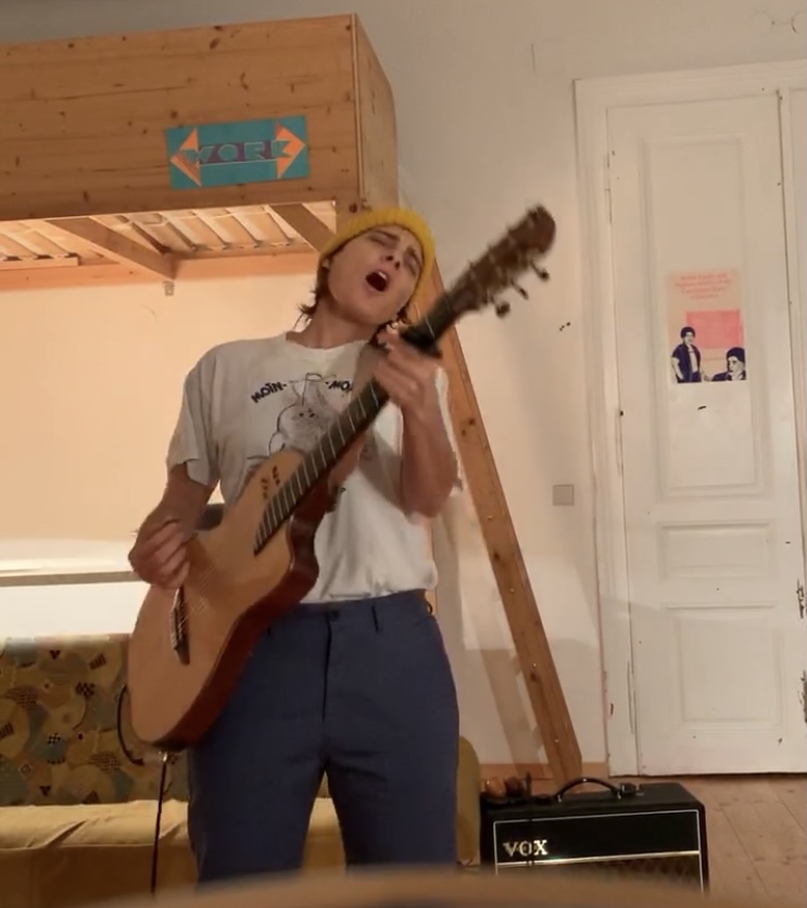 """Daniela during quarantine playing a cover of Brontez Purnell's """"The Reason Why I Can't Fucking Stand You"""" in a beanie and t-shirt"""